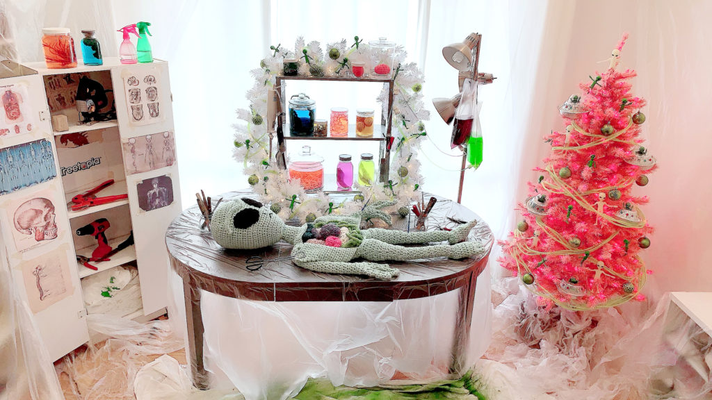 Alien Autopsy Halloween decor with crocheted alien and pink Halloween tree covered in UFOs
