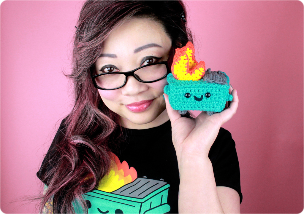 Twinkie Chan and her crocheted dumpster fire, also wearing a black dumpster fire t shirt by 100% Soft