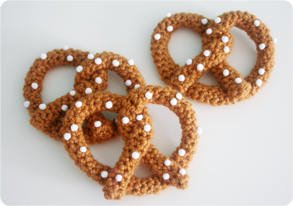 Three crocheted pretzels covered in small white pompom salt.