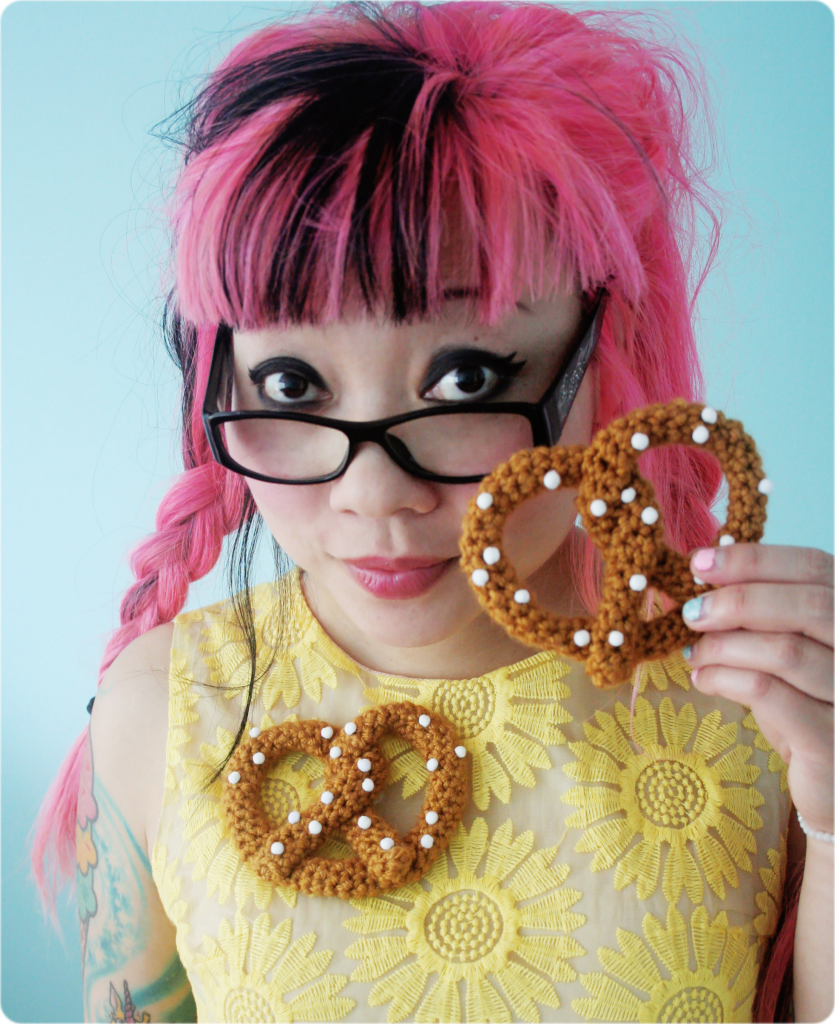 Twinkie Chan wears a yellow floral dress and a crocheted pretzel brooch. She is also holing a crocheted pretzel in her hand.